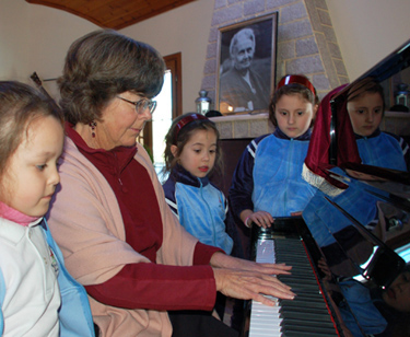 Susan playing the piano for school guests